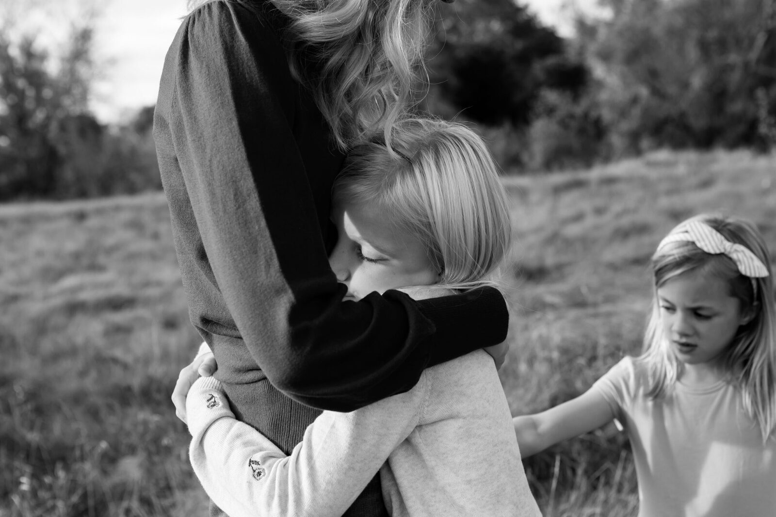 daughter embraces her mom with eyes closed