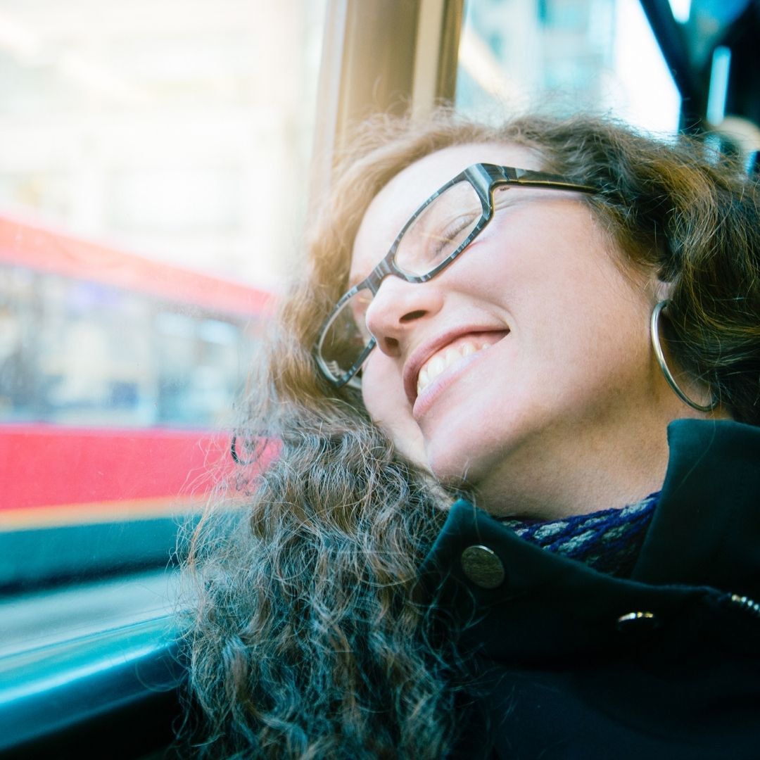 girl on the bus laughing looking outside