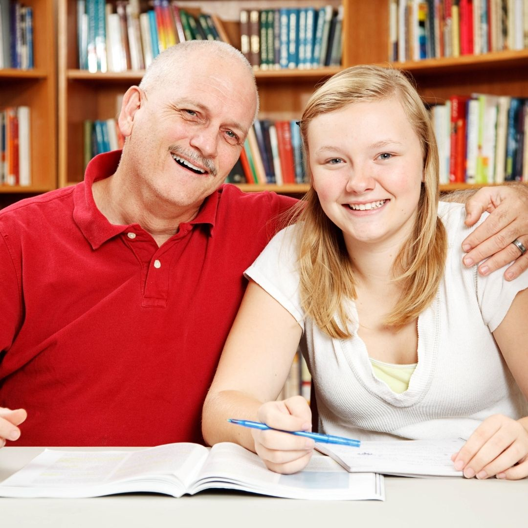 Dad and daugther posing for picture studying in the library