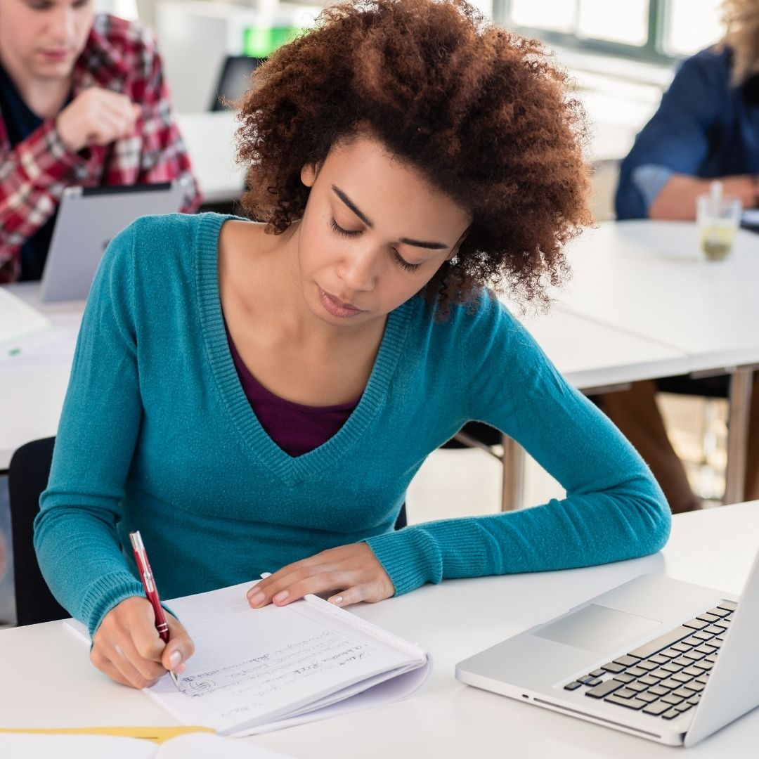 girl student writing an essay in class