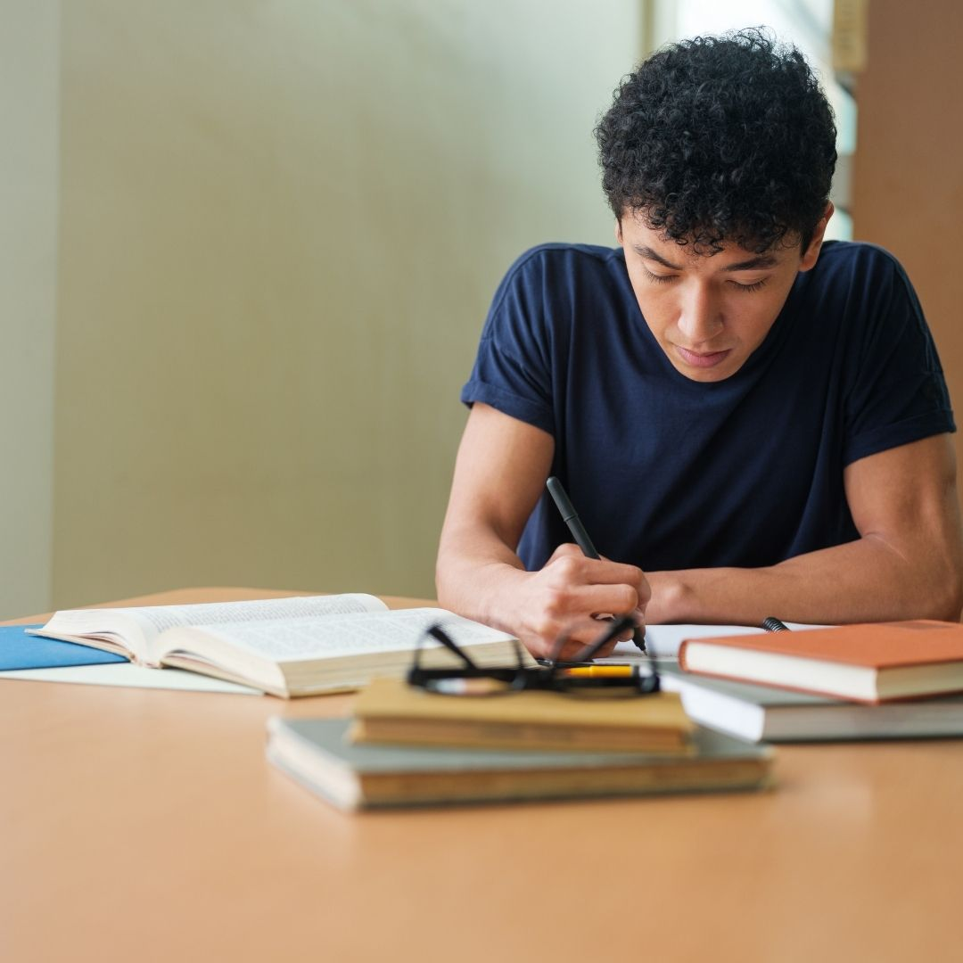 Boy student writing in notebook