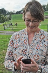 Woman Looking at Smart Phone App with Horses in Field Behind Her