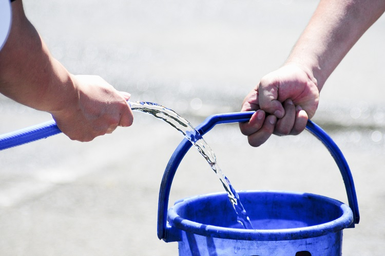 Filling up bucket of water from hose without allowing the hose to touch the bucket or to be submerged. This is the correct way to fill horse water buckets for biosecurity best practices.