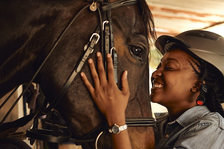 Young black woman smiling at a horse and embracing the sides of face shows that she clearly loves this horse