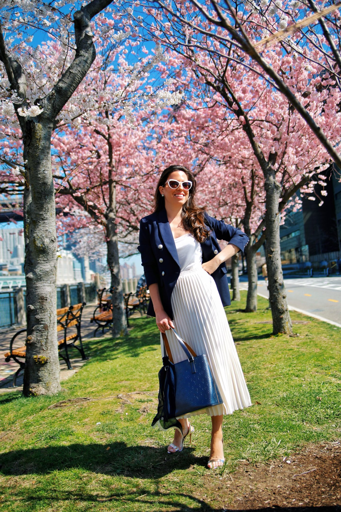 Ana Florentina wearing navy blazer and white pleated skirt spring outfit