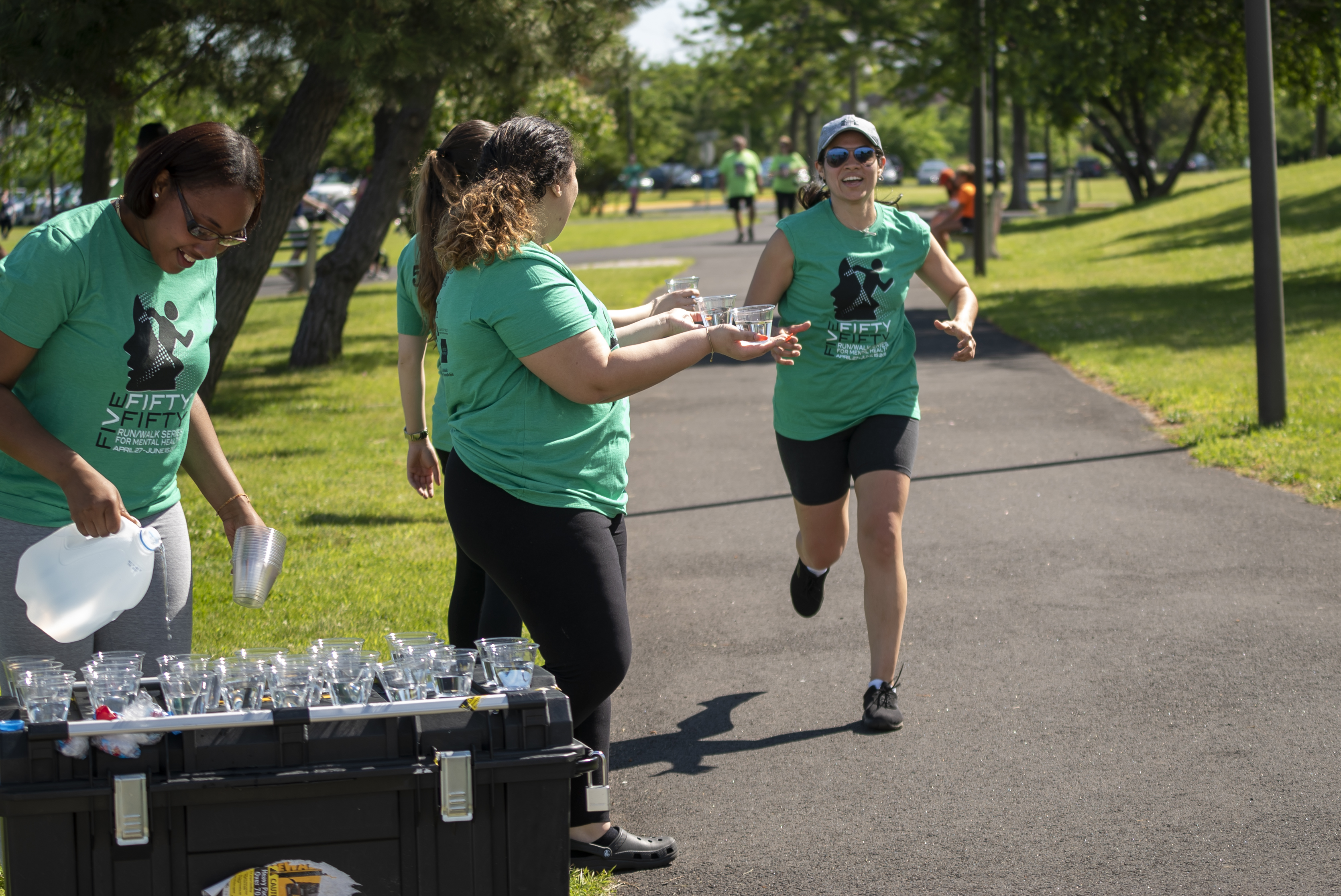 Five Fifty Fifty volunteers hand water cups to runners.