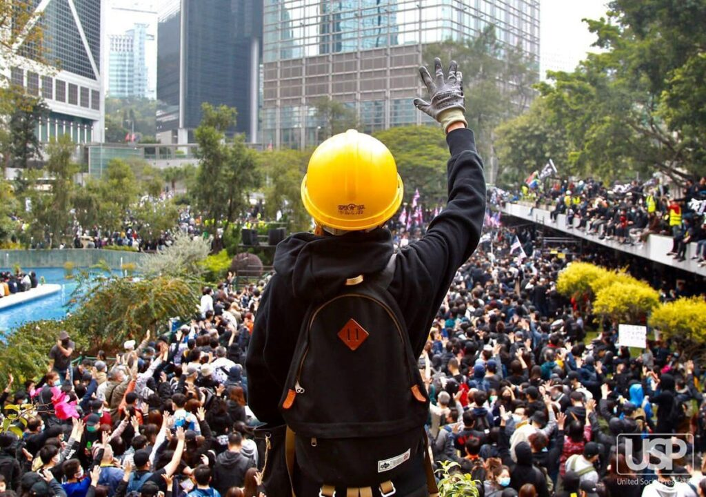 A protestor in a yellow hard hat and a backpack, facing away from the camera and holding up a gloved hand towards a large crowd of protestors below