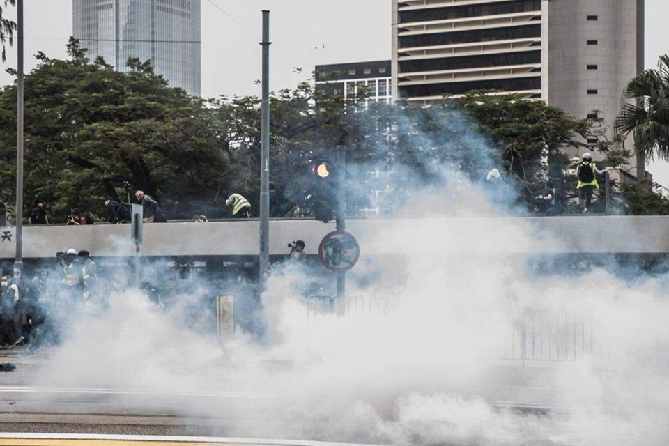 Tear gas rising from a street as protestors flee over a fence