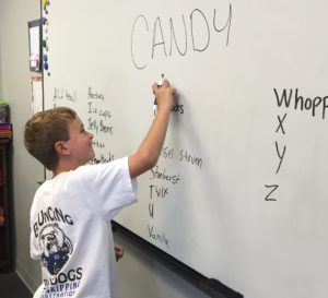 Students writing the names of candy A to Z