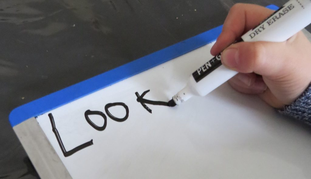A student writes the word LOOK on an individual whiteboard.