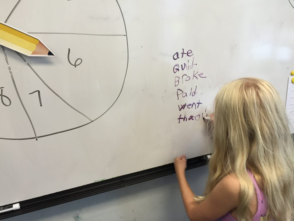 A child writes a list of Irregular past verbs