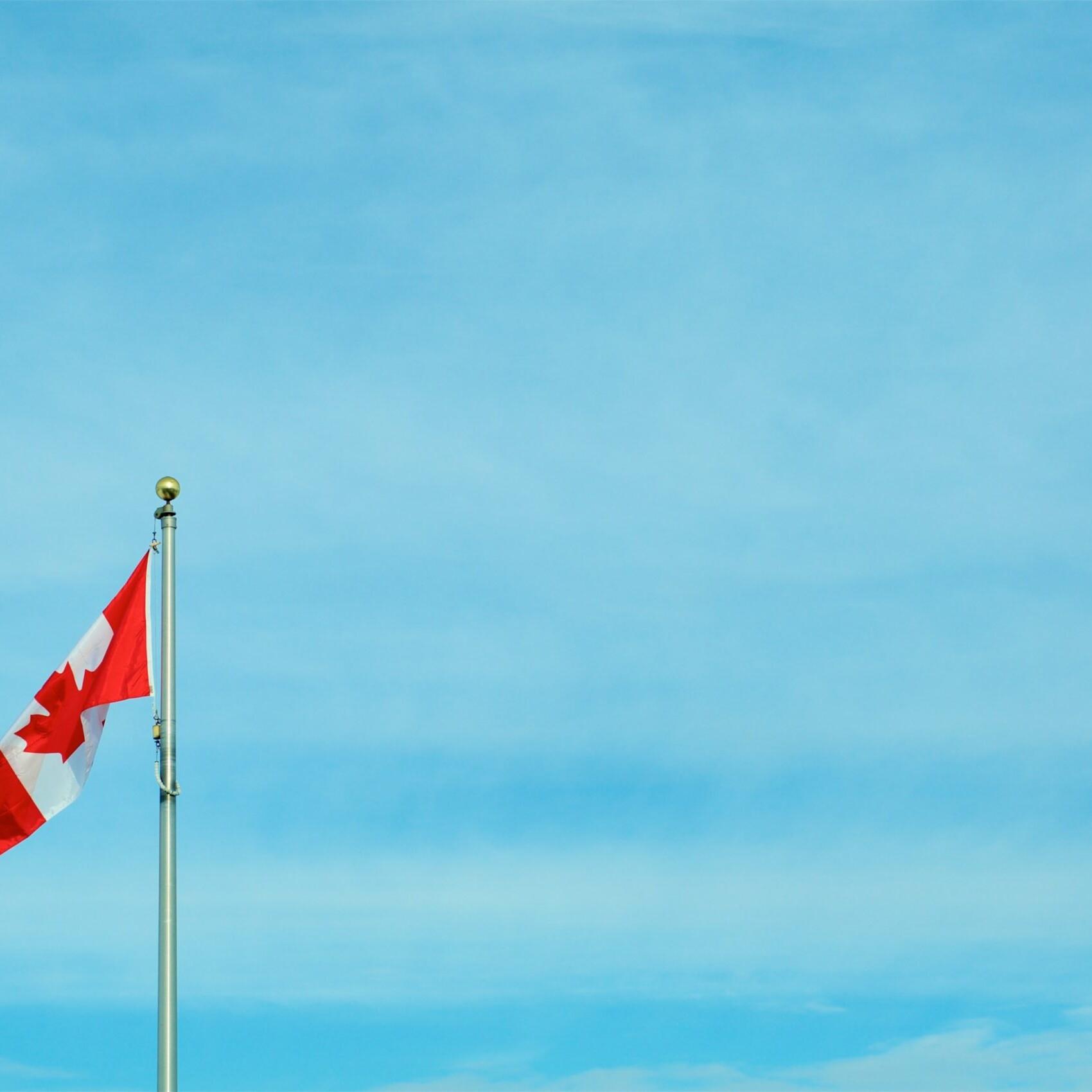 Canadian flag against blue sky.
