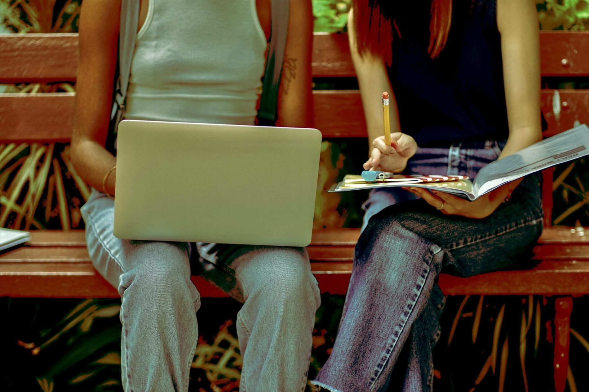 Two young women with laptop on bench