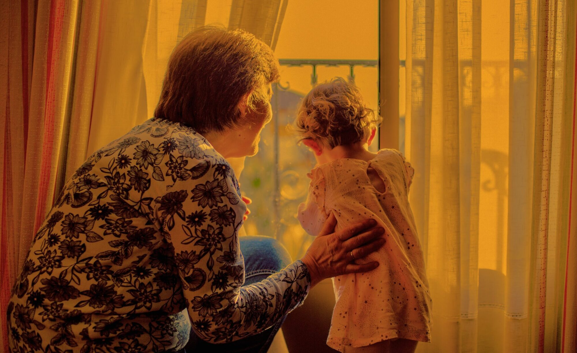Older woman and toddler look out window