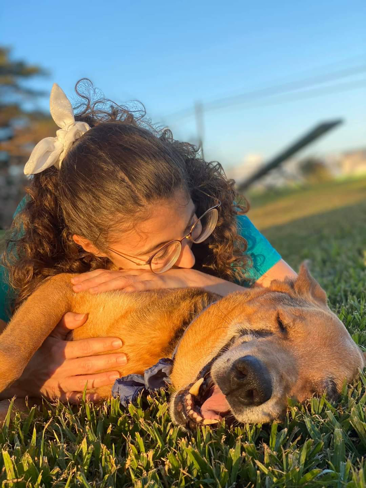 Dog and girl laying in the grass
