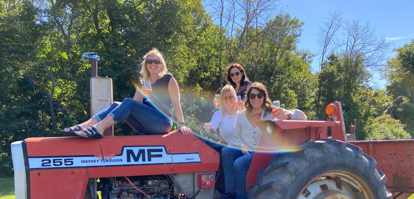 Ladies posing on a tractor with wine in hand