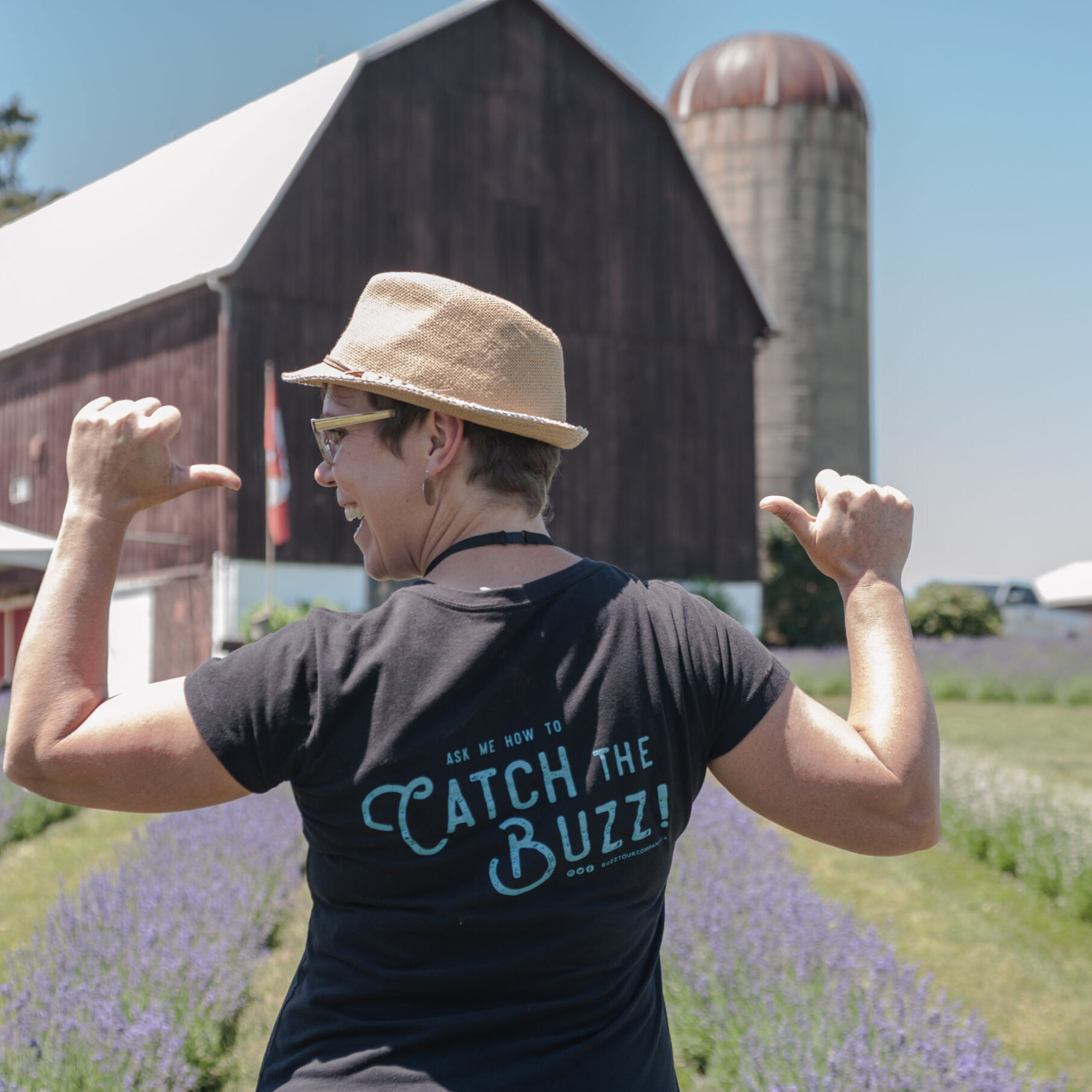 """Tour guide pointing to back of shirt that says """"catch the buzz"""""""