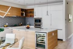 Island Kitchen with rift white oak cabinet and paint grade refrigerator panels