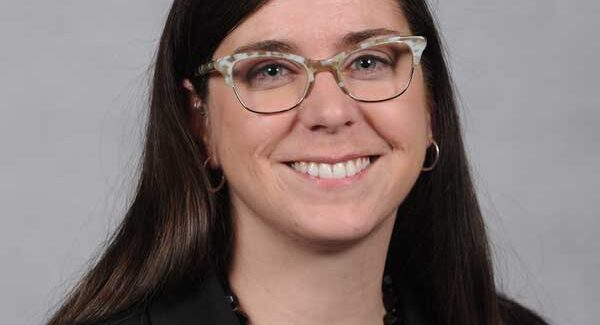Profile picture of Megan Quinn (a caucasian woman similing at the camera while wearing glasses)