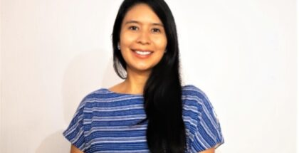 Picture of Alejandra Rivera, a woman wearing a blue striped top with black hair falling over her left shoulder