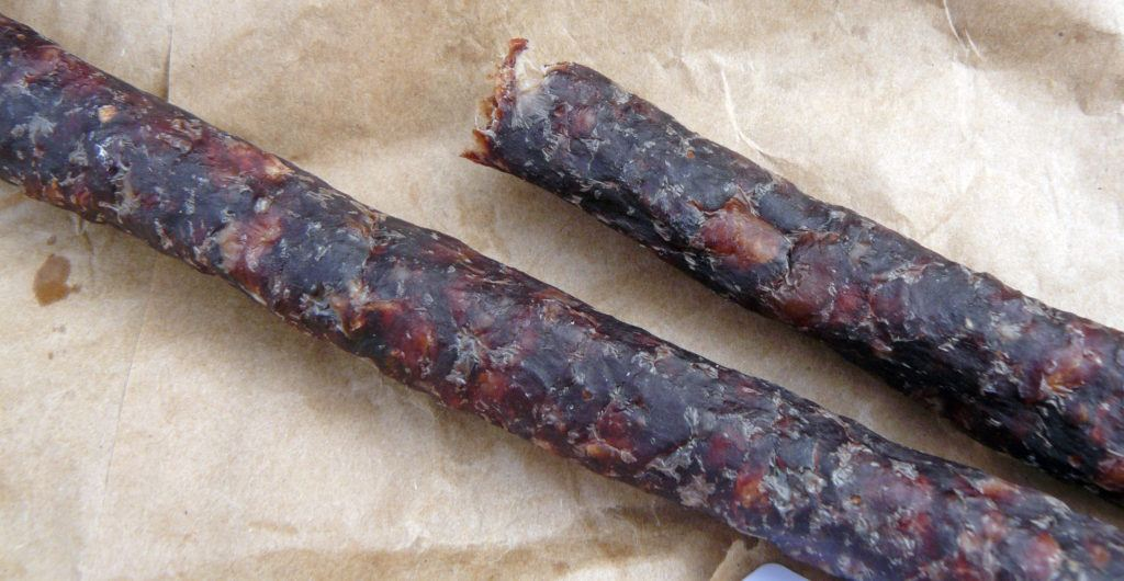 An image of two cured sticks of droëwors sausage on a brown paper bag