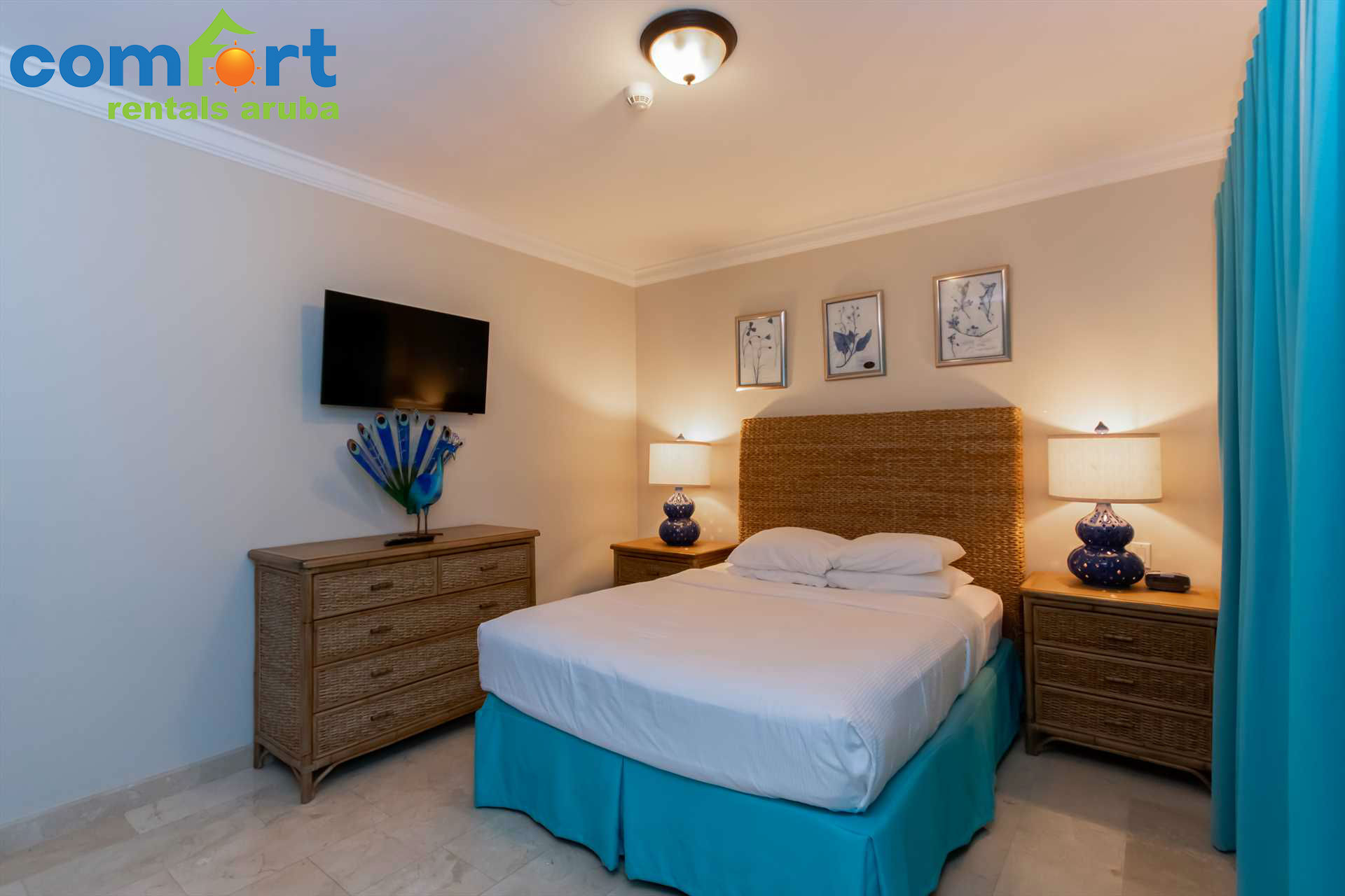 Second bedroom with a beautiful combination of tropical colors and a TV