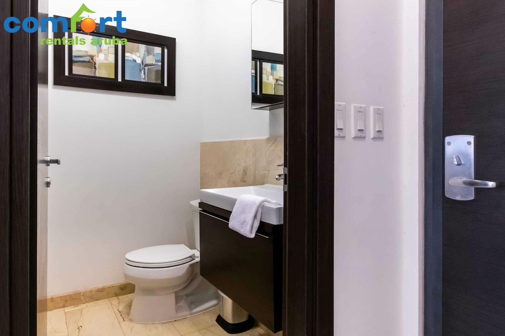 A half bathroom is conveniently located in the corridor