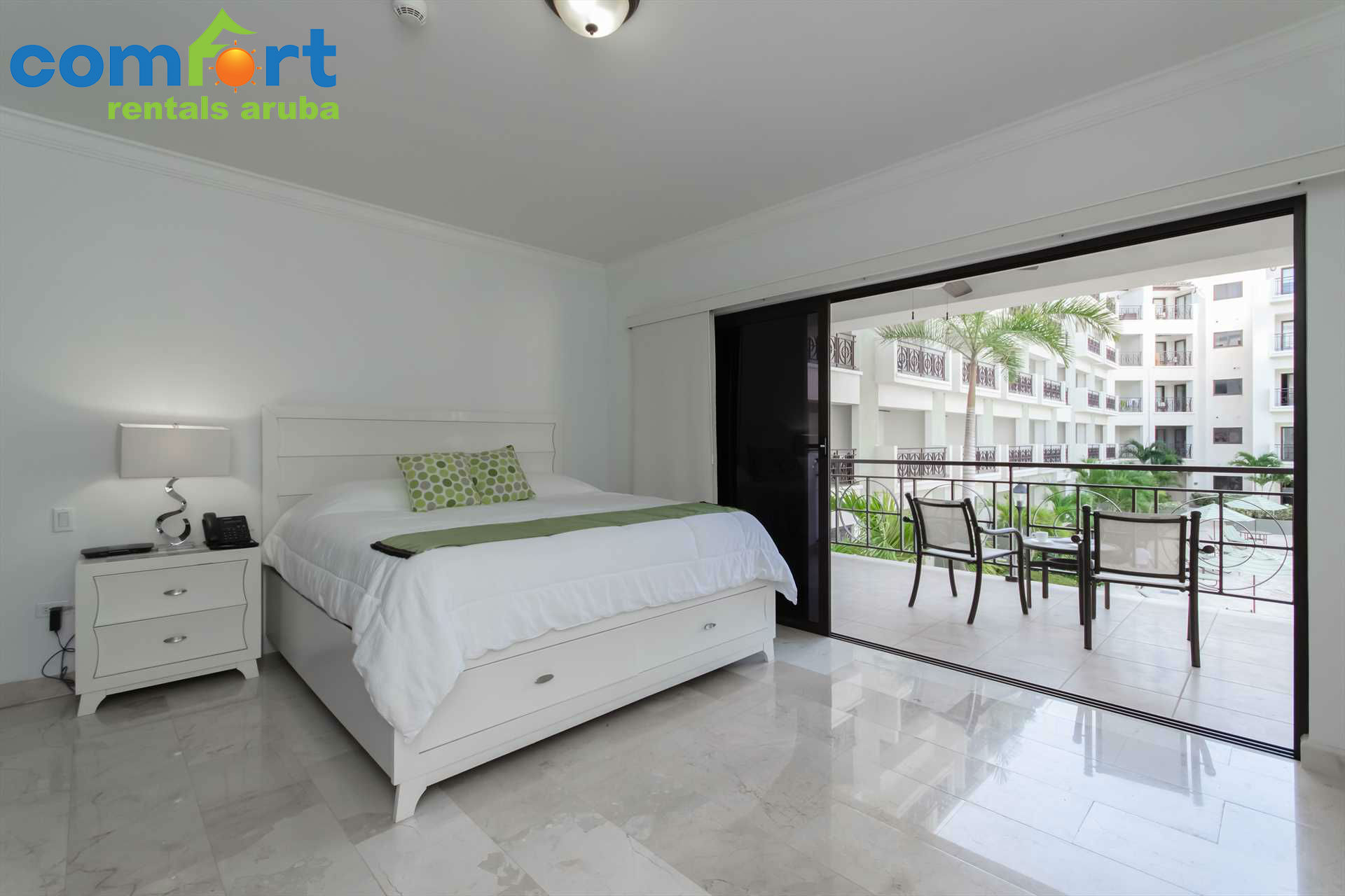 The master bedroom with a king-size bed and access to the balcony