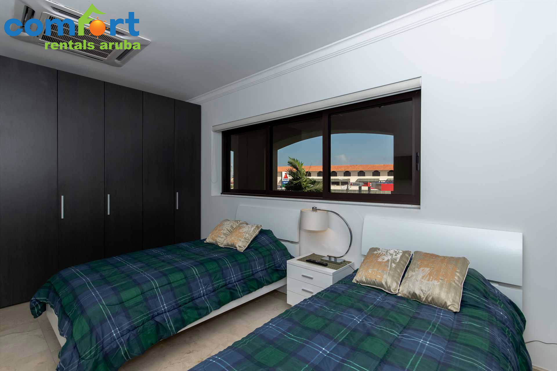 The second bedroom with two single beds and a built-in closet