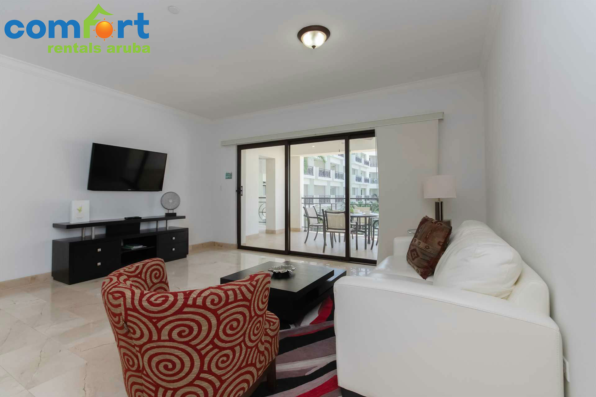 Cozy living room with a sofa, an accent piece chair and easy access to the balcony