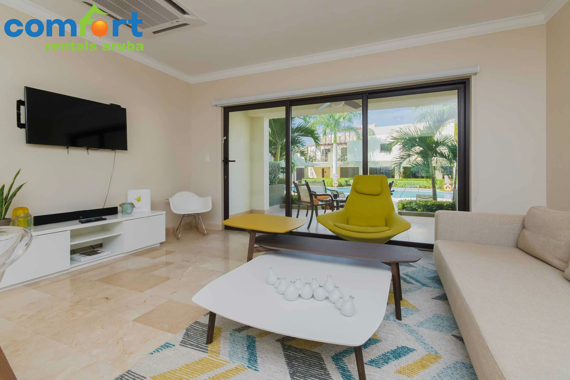 Living room with a TV and access to the terrace with stairs leading to the resort pool