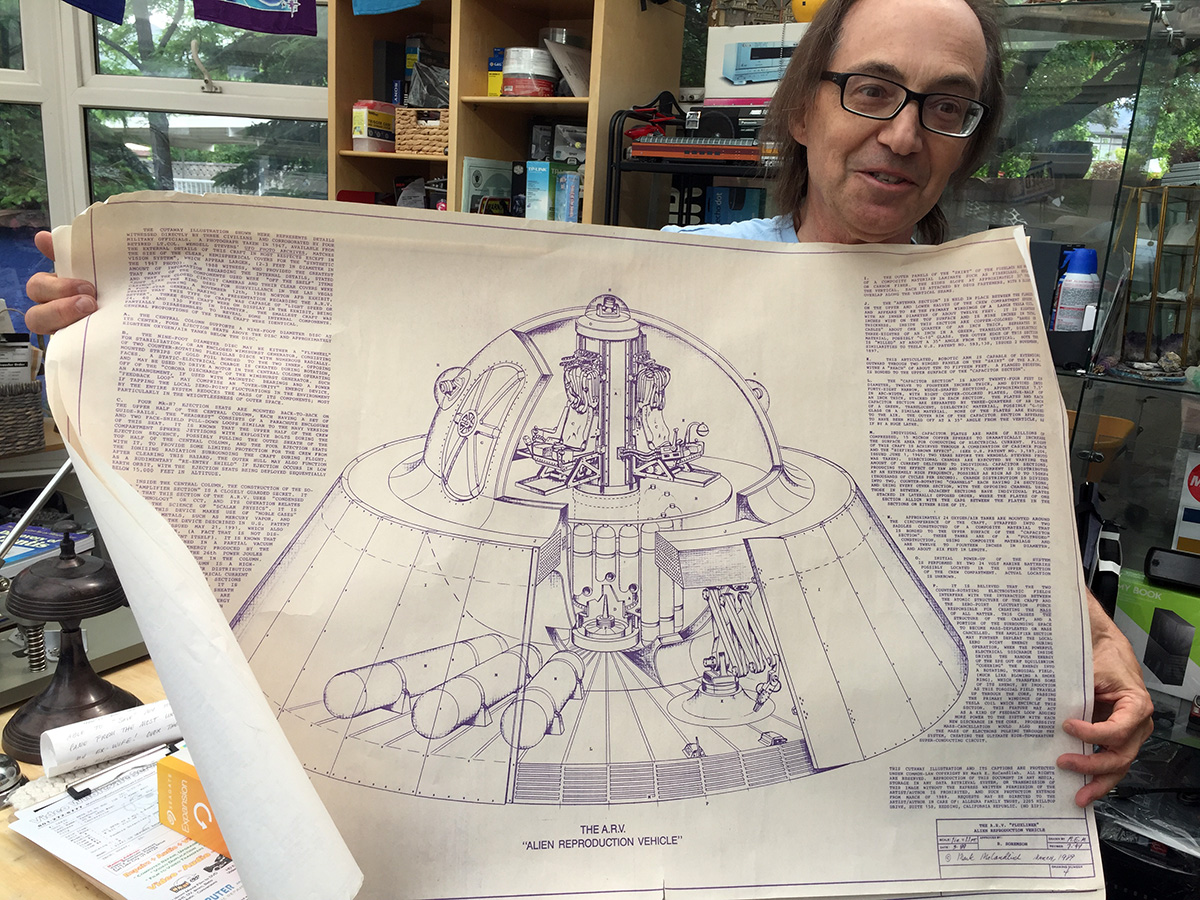 Mark holds up a schematic of an alien spacecraft.