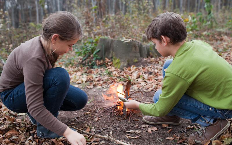 Boy and girl making campfire in forest