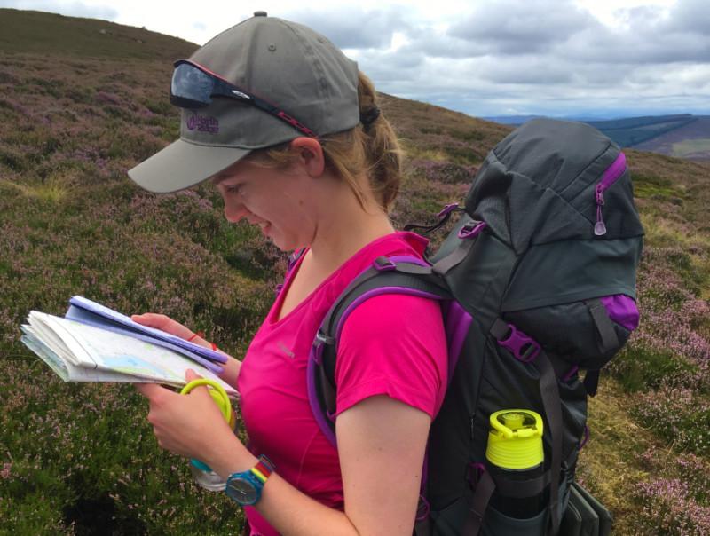 Woman navigating on hillside
