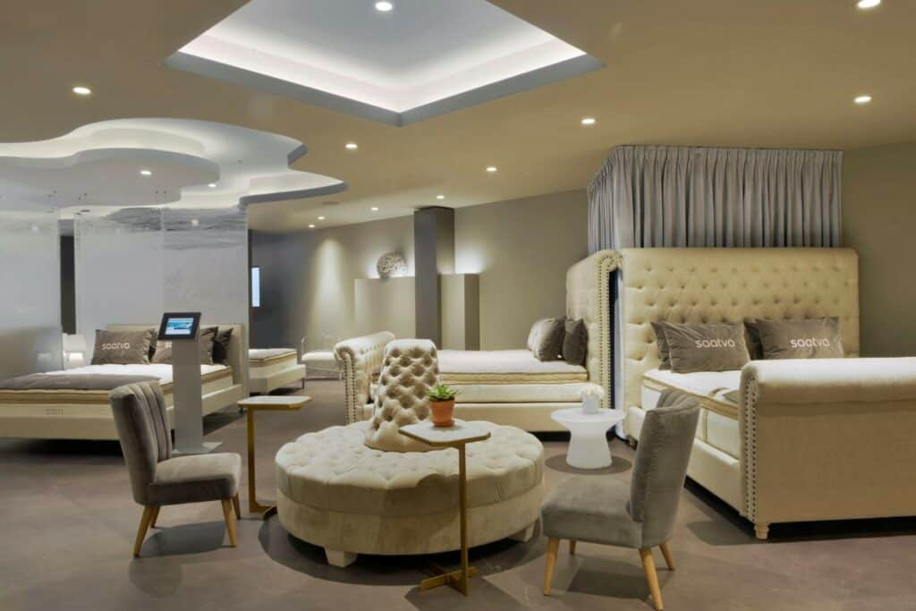 Using a Greek-inspired motif, beds displays are accompanied by relaxed lighting and furnishings under cove-lit recessed ceiling with cutouts referencing the sky – ceiling is painted PPG's Lazy Afternoon, coves painted PPG's Duck's Egg Blue