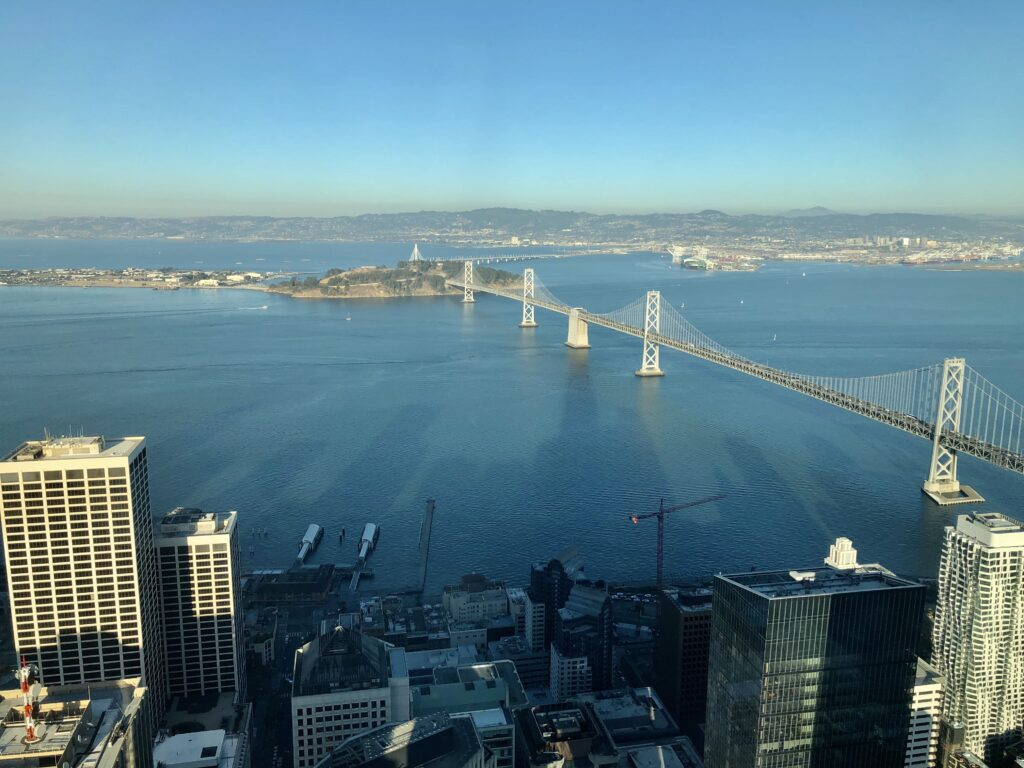 Photograph of the San Francisco Bay from the top of a tall tower in San Francisco. The shadow of the city skyline is seen on the water. The Bay Bridge extends from the bottom right to the middle of the screen where it lands on Treasure Island. The East Bay cities of Oakland and Berkeley can be seen in the distance.