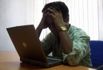 Frustrated collapsed expression of a laptop user
