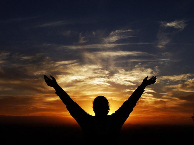 Raised hands at sunset