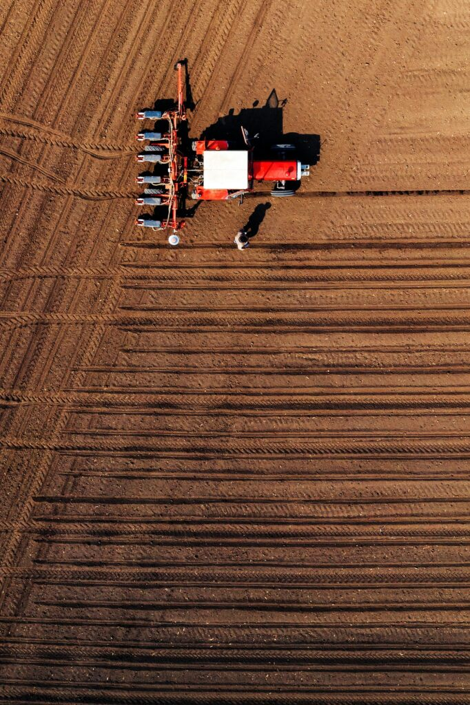Aerial view of farmer and tractor with crop seeder