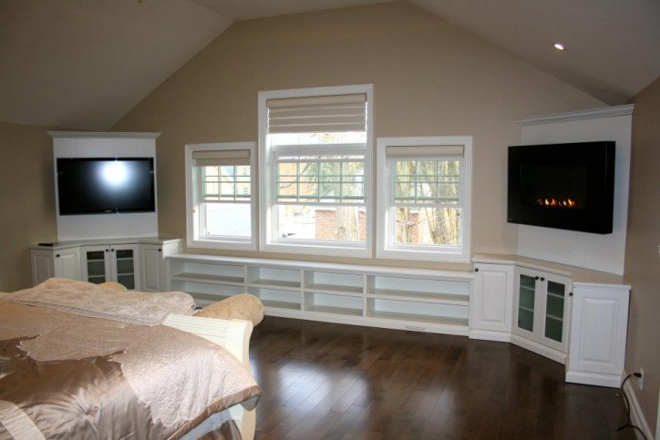 bedroom cabinetry with fireplace and television
