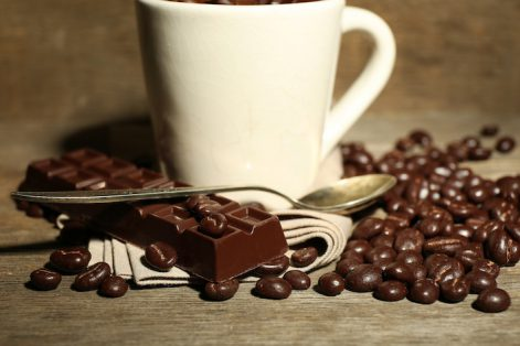 Cup with coffee beans and dark chocolate glaze on wooden background