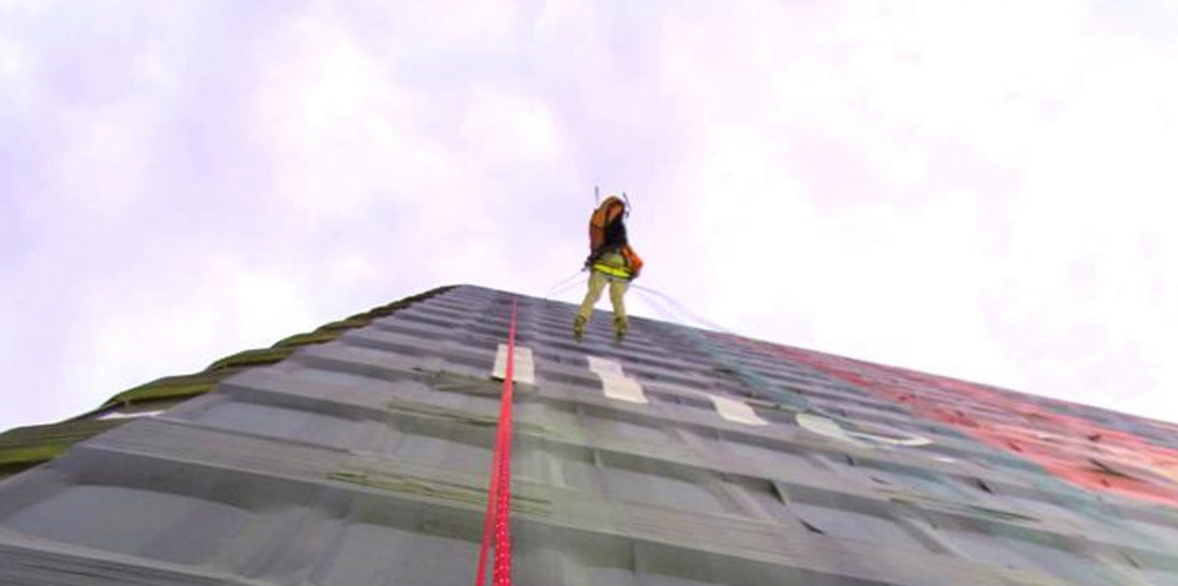 person rappelling down a building with a large format banner