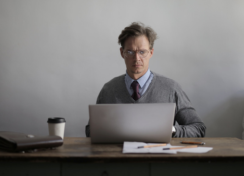 Canva-Concentrated-teacher-using-laptop-in-office