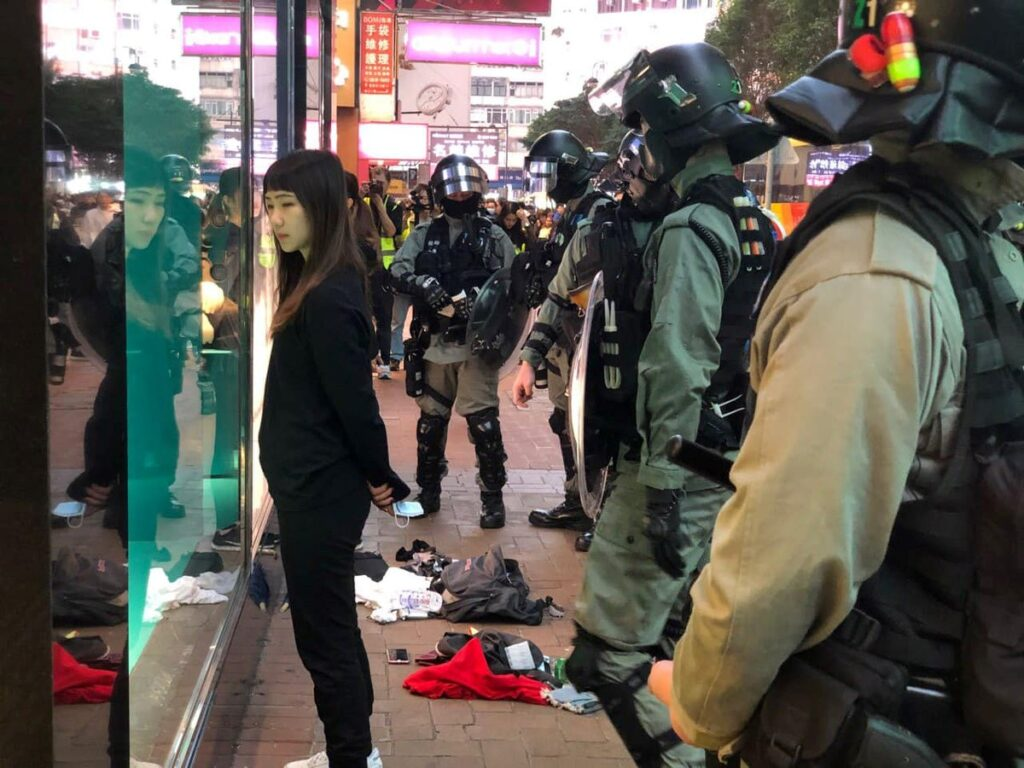 A woman dressed in black looks at her reflection in a shop window, surrounded by officers in riot gear