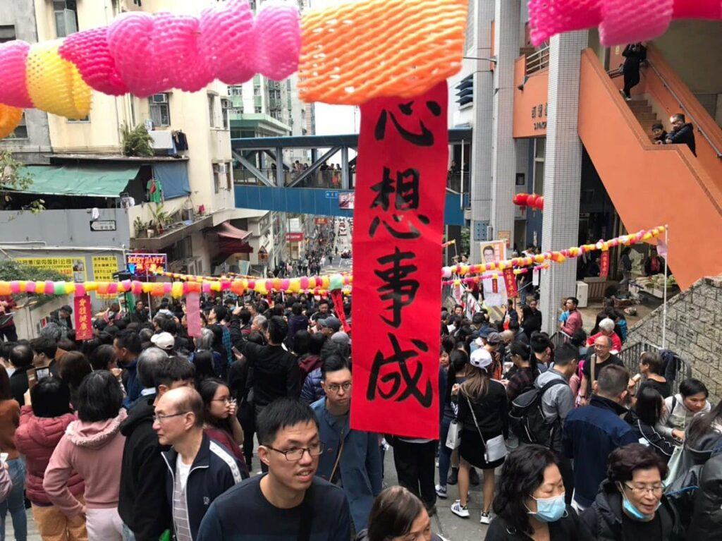 Milling crowds in a Hong Kong street with holiday decorations of a vertical red banner with Chinese writing and colorful paper chains stretched across the street