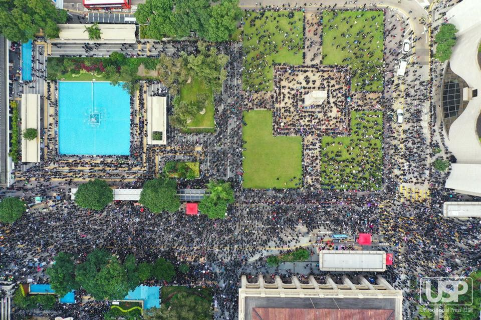 An aerial view of a square, including fountains, geometrical lawns, and trees, full of thousands of protestors