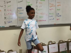 a student standing in front of a group speaking a fact or opinion