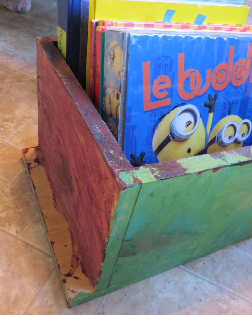 a painted wooden box full of books