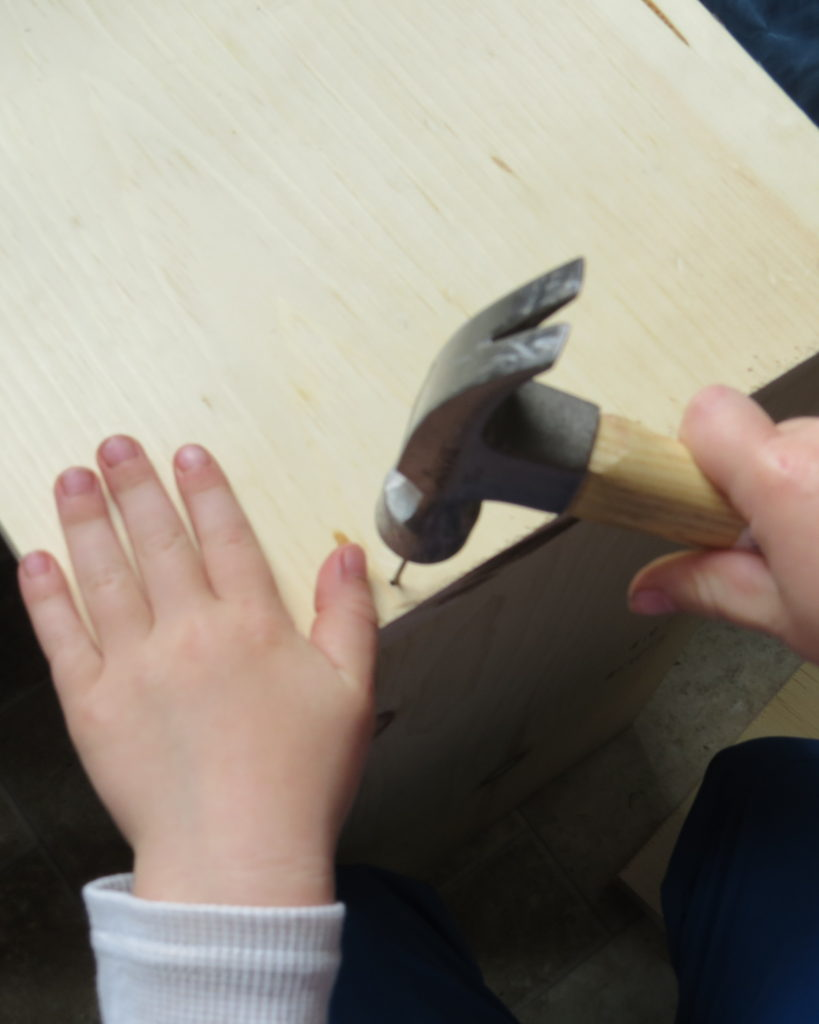 a child hammering in a nail