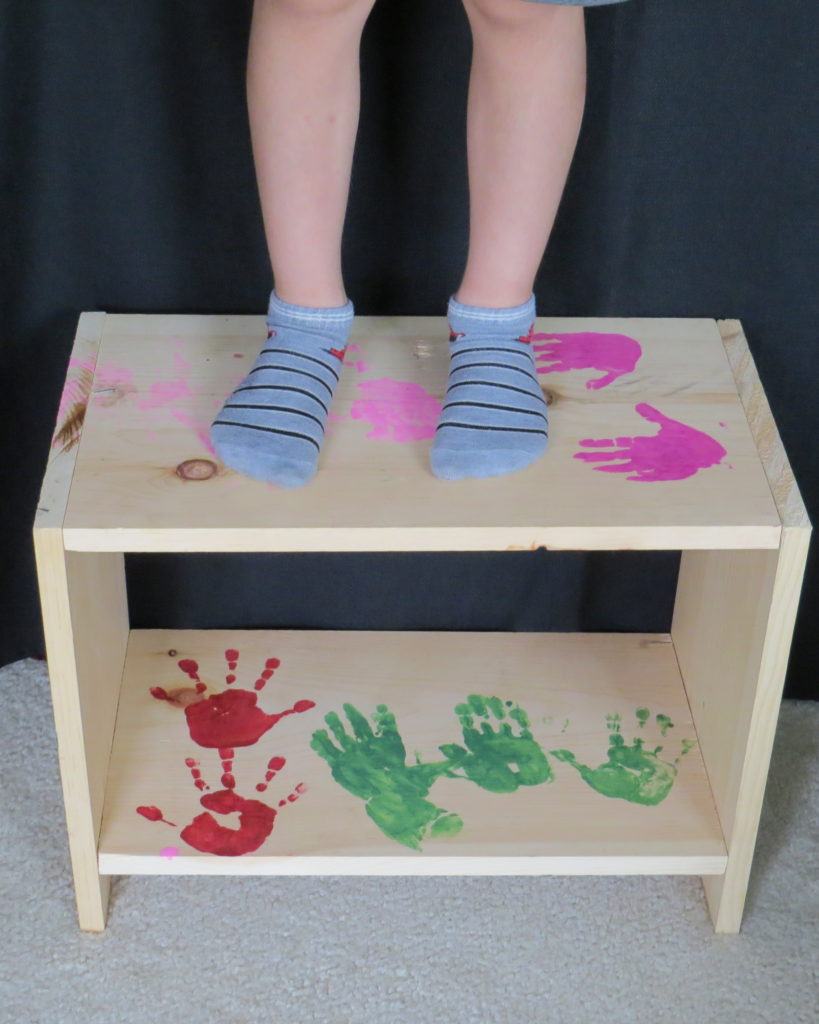 A child standing on a wooden shelf